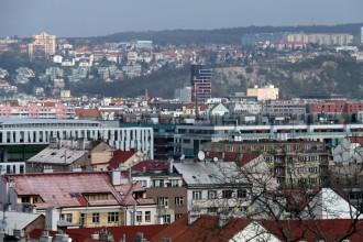 Pohled přes Karlín, Holešovice, v pozadí moderní budova v holešovickém pivovaru, na horizontu Ďáblice