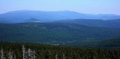 Krkonoše v pozadí, vlevo Vysoké kolo a vpravo Kotel, vrcholy okolo 1500 metrů. Vlevo poblíž homole Bukovce. Úplně vpravo sjezdovky na Čertově hoře nad Harrachovem.