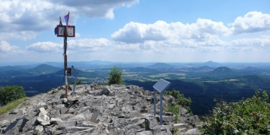 Vrcholek Klíče (759 m) v Lužických horách, pohled směrem k východu. Vlevo u tyče na horizontu Ještěd, vpravo na horizontu vystupuje Ralsko.
