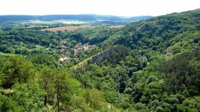 Ze skal nad Hostimí - pohled k jihu, do údolí Loděnice. Skála stojí kolmo k toku říčky, ta ji v jednom místě prorazila.