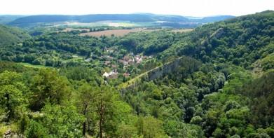 Vyhlídka do údolí říčky Loděnice v Českém krasu, dole obec Hostim. Říčka si prorazila cestu skálou, která leží kolmo k jejímu toku.